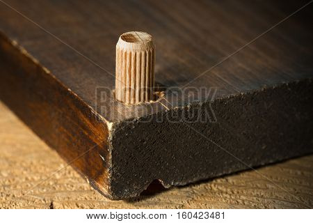 Macro photography of a wooden dowel in the hole of a wooden board