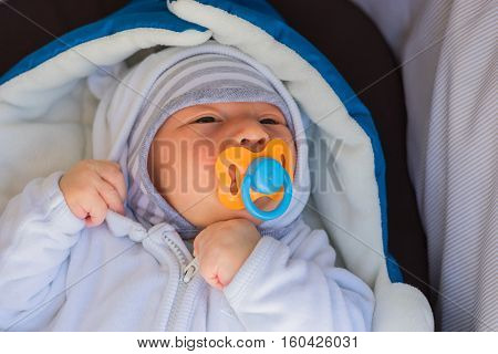 Newborn baby lying in a stroller with nipple in his mouth. Baby wrapped in warm clothes lying in a stroller.