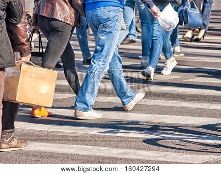 pedestrians walking on a pedestrian crossing on sunny day