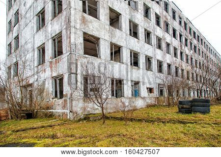 old abandoned high-rise building on gloomy cold autumn day