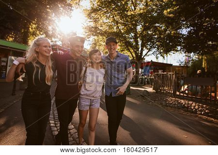 A group of best friends hanging out together and walking through a park. Friends all having a good time and smiling.