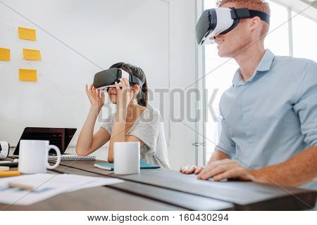Young man and woman sitting at a table and using virtual reality goggles. Business team using virtual reality headset in office meeting.