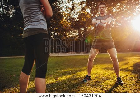 Young Man Doing Kettlebell Workout With Personal Trainer