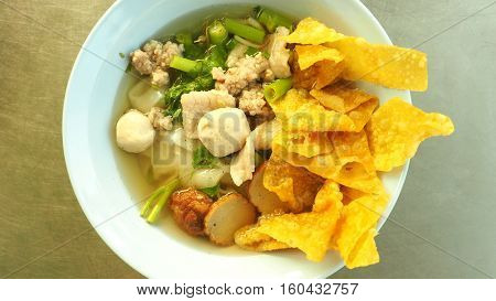Thai noodle fish and pork soup have flat pork ball fish morning glory parsley green onions sliced Fried Wonton crisp soup shrimp dumplings in white plastic bowls.