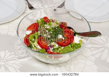 Fresh salad in the glass bowl on the table