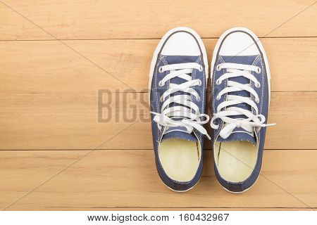 Blue running shoe (sneakers) on wooden background