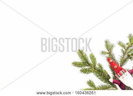 Christmas composition. Green fir twings and Xmas decoration Santa on white background. Top view, flat lay. Copy space for text. Winter holidays concept