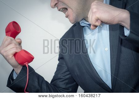 Young businessman with the phone, angry-violent. The Boss informs him that has screwed up.