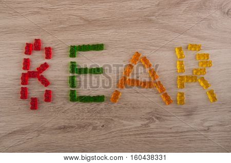 word bear made of red green orange yellow gelatin sweets on wooden background