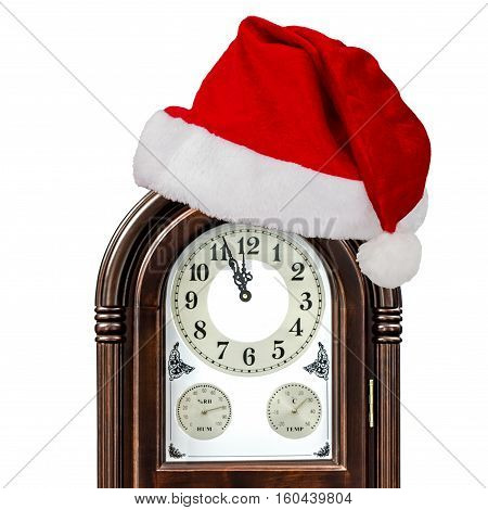 Grandfather clock and cap of Santa Claus isolated on white background