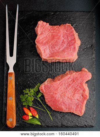 Raw Fresh Marbled Meat Steak Filet Mignon And Meat Fork On Slate Plate With Parsley And Chili Black