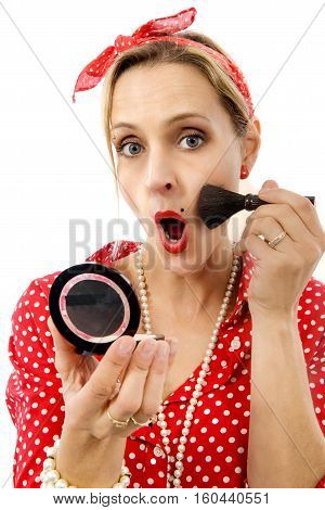 pretty blond pin up girl applying blusher isolated on white background