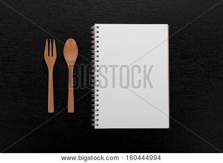 notebook and wooden spoon fork on black wooden background
