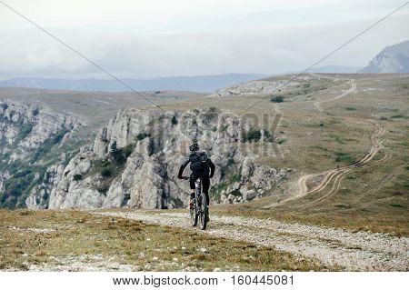 athlete cyclist on mountainbike rides along trail c