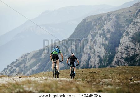 two athletes cyclists on mountenbike riding a mountain trail on mountain landscape