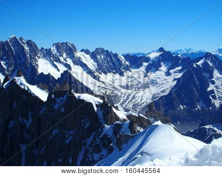 Alpine mountains range in beauty French, Italian and Swiss Alps seen from Aiguille du Midi with clear blue sky in warm and sunny summer day, CHAMONIX MONT BLANC, FRANCE in JULY 2016.