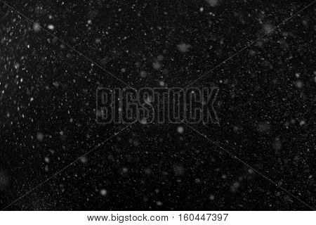 The falling snow on black background. Texture.
