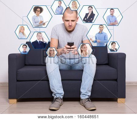 internet concept and social media concept - handsome man sitting on sofa and using smart phone