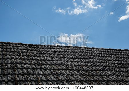 Aged roofing tiles on old house in village. A lot of moss on tiled roof of hovel against blue cloudy sky. Countryside scene