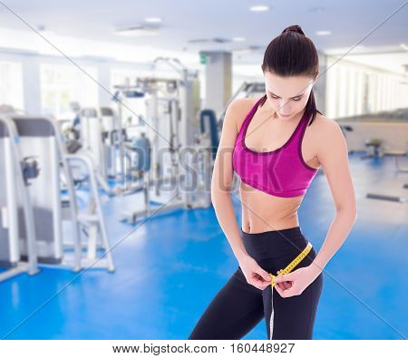 sport concept - beautiful slim sporty woman measuring her waistline with measure tape in the gym