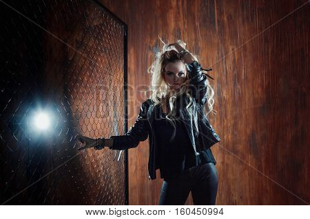 Rock'n'roll girl, young beautiful girl dances in a dark alley, against the fence mesh