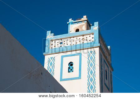 Blue and white architecture typical for the area by the Atlantic ocean. Minaret of a mosque with a blue bright sky in the background. Sidi Ifni Morocco.