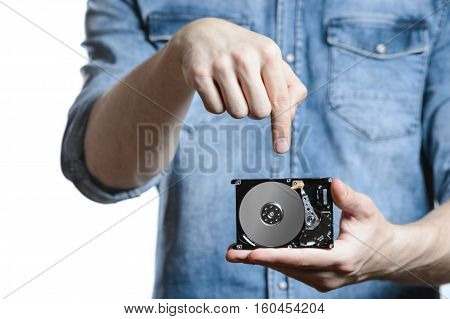 Man's hand holds a 2.5 inch hard drive. He's points to the hard disk. View of the backside HDD, from the PCB. Isolated on white background.