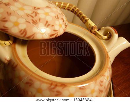 tetera de diseño florar que contiene té verde en su interior