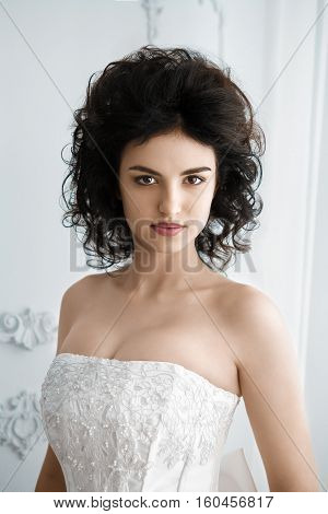 Pretty bride with the nice makeup. Sexy woman wearing wedding dress, black hair.