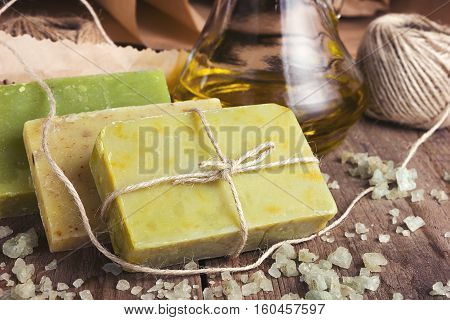 Collection of handmade, natural organic soap and cosmetic oil on wooden background. Spa products. Purple and vintage tinted