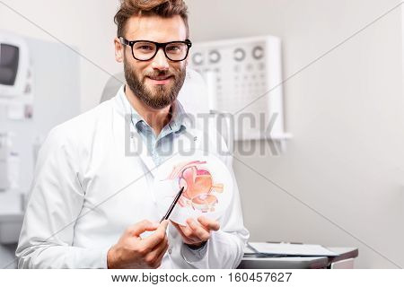 Portrait of handsome ophthalmologist with eye model in front of the eye chart in the cabinet