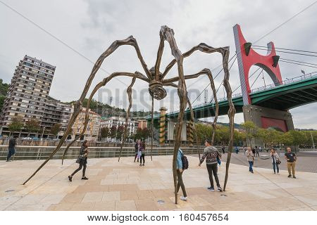 Bilbao Spain - October 16: Group of tourist visiting Louise Bourgeois giant 11 meter high spider at the back of the Guggenheim museum on October 16 2016 in Bilbao Spain.