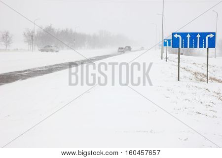 Cars on winter road in a snowstorm and bad visibility