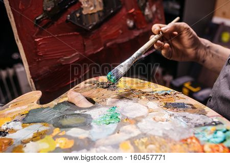 Artist holds a palette and a brush, paints a picture. Creative process of drawing in workroom. Cropped image