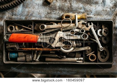 Box with tools in the workshop on a dirty dusty background. Wrench with orange handles, screws, bolts, wrenches and other tools