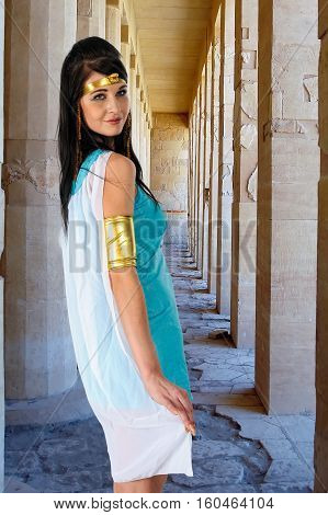Pretty woman in egyptian queen costume near colonnade of Birth in Deir El-Bahri Temple of Queen Hatshepsut
