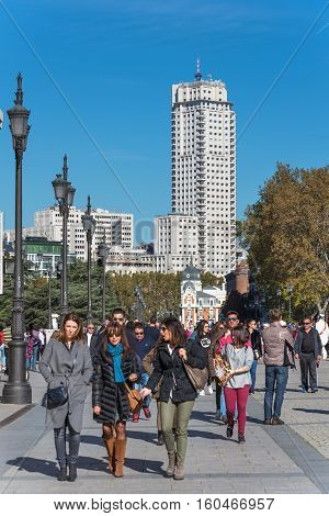 MADRID SPAIN - NOVEMBER 13: Tourist visiting Madrid with Madrid Tower skyscraper in the background (shallow Dof focus on the people) on November 13 2016 in Madrid Spain.