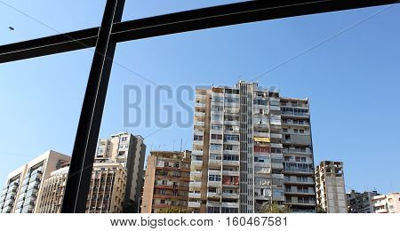 An old building in Lebanon with a bird flying into the frame of metal.