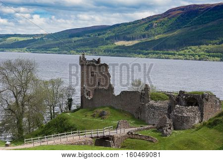 Loch Ness Scotland - June 2 2012: The ruins of Urquhart Castle sit on a green cliff looking over Loch Ness. Surrounding green hills. Light blue sky with white clouds.