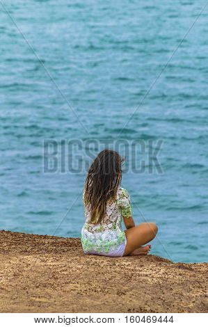 Young attractive woman sitting at edge of rocky hill with the ocean at the background in Pipa Brazil