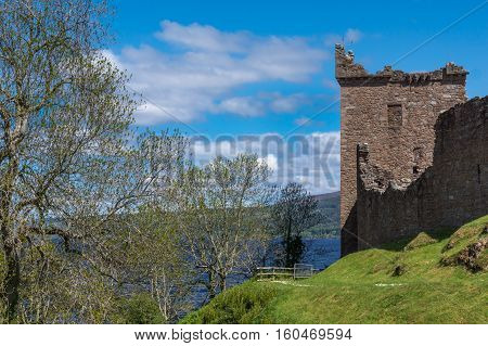 Loch Ness Scotland - June 2 2012: Shot of the main ruin the tower of Urquhart Castle in combination with trees. Deep Blue Loch Ness visible in back. Green surrounding hills. Blue sky and white clouds.