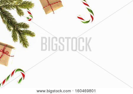 Christmas composition. Green fir twings, Xmas gifts and candy canes on white background. Top view, flat lay. Copy space for text. Winter holidays concept