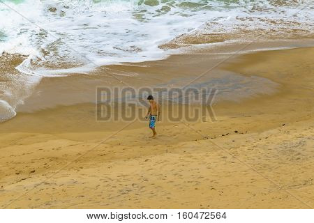 PIPA, BRAZIL, JANUARY - 2016 - Top view shot of young man walking at empty beach in Pipa Brazil