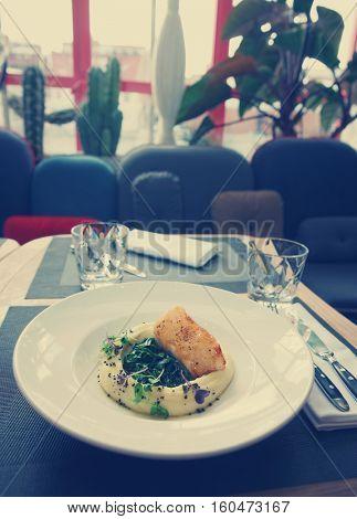 Fried black cod fillet with potato mash on restaurant table