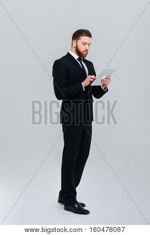 Full length young bearded business man in black suit standing sideways and writing message on tablet computer. Isolated gray background