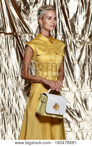 fashion studio photo of beautiful blonde woman with bright makeup wearing crown in hair in yellow dress; hold the bag in hands