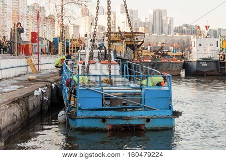 MOSCOW, RUSSIA - NOVEMBER 11, 2016: State Unitary Enterprise Mosvodostok performs recovery vessels on coastal winter parking. Two workers unhooks the load hook.