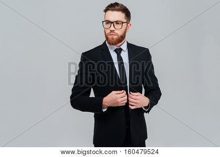 Cool bearded business man in glasses and black suit looking aside. Isolated gray background