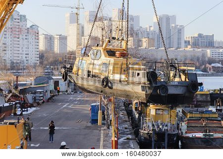 MOSCOW, RUSSIA - NOVEMBER 11, 2016: State Unitary Enterprise Mosvodostok performs recovery vessels on coastal winter parking. River boat transported by crane.