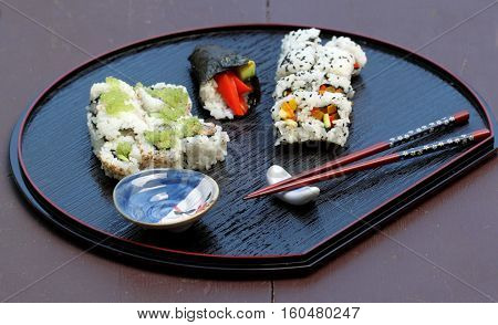 Different types of sushi on a serving plate.